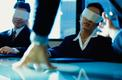 Two blindfolded business executives at a desk
